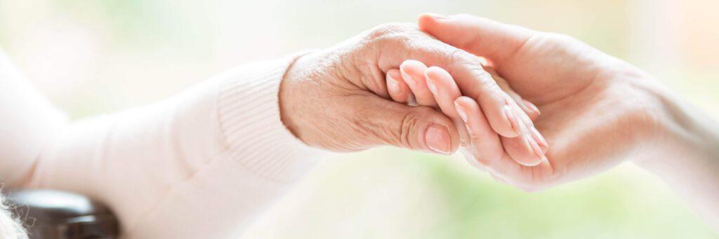 Pflegefachfrau haelt liebevoll die Hand einer Patientin