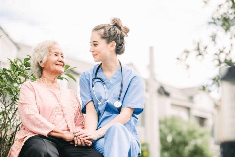 Pflegefachfrau spricht mit aelterer Dame